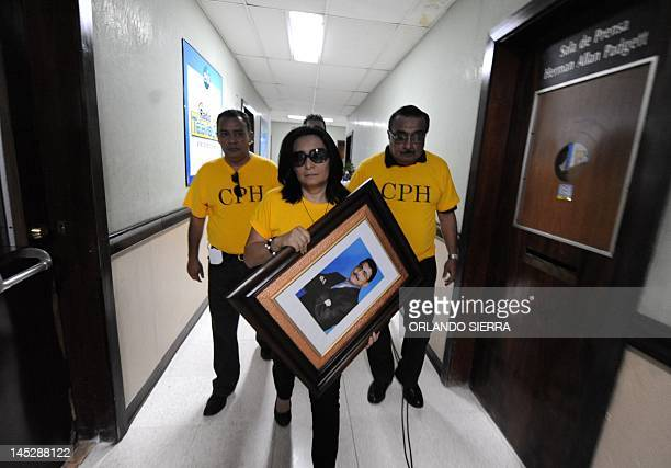 A portrait of murdered journalist Alfredo Villatoro is taken by his widow Karen to be hung on the wall of which was his cabin at the HRN la Voz de...