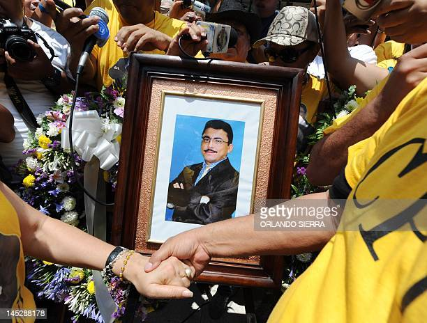 A portrait of murdered journalist Alfredo Villatoro of HRN la Voz de Honduras broadcasting is held by friends and colleagues during the celebration...