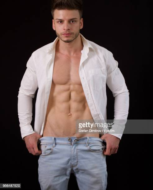 portrait of muscular man standing against black background - fully unbuttoned stock pictures, royalty-free photos & images