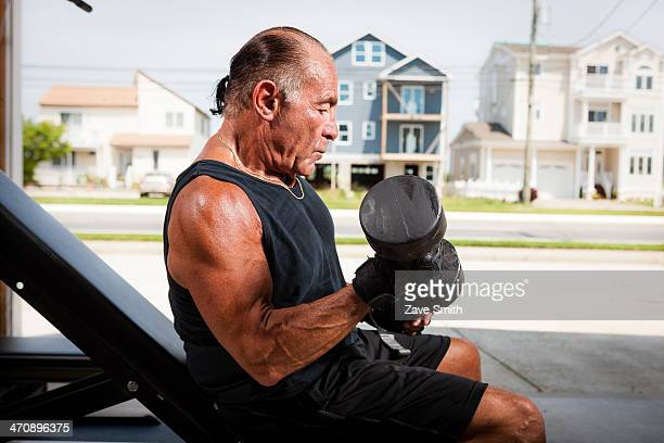 Portrait of muscular senior man lifting dumb bells