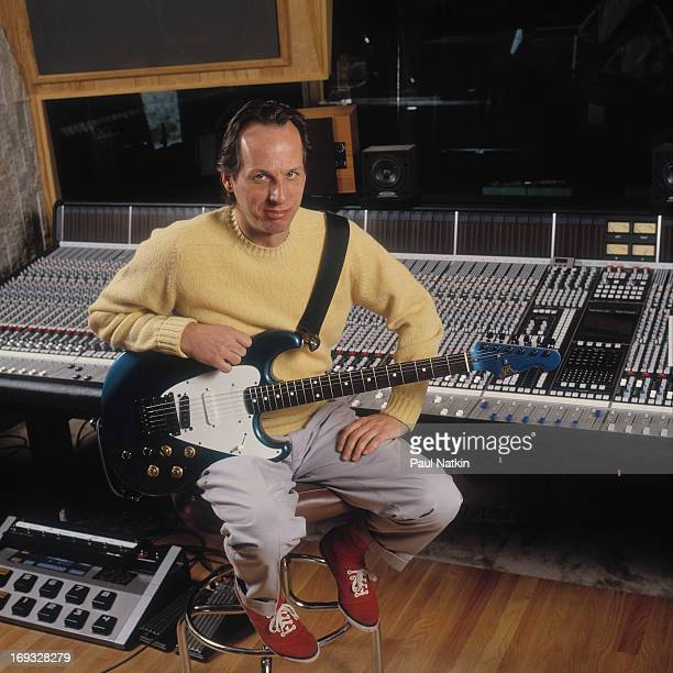Portrait of musician Adrian Belew as he sits on an amplifier with a guitar on his lap Lake Geneva Wisconsin April 15 1994