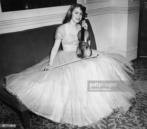 Portrait of musician Camilla Wicks wearing an evening gown and holding her £15000 Strad violin London November 30th 1950