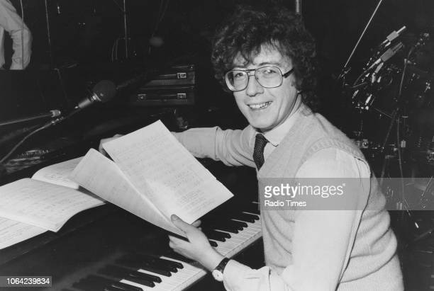 Portrait of musician Chris Stuart sitting at a piano with sheet music November 21st 1979