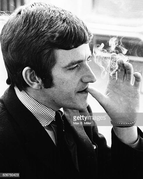 Portrait of musician Dave Clark of the band 'The Dave Clark Five' smoking a cigarette circa 1965