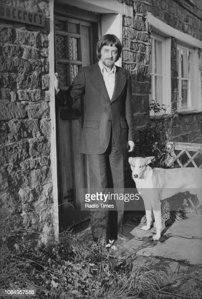 Portrait of musician Dave Swarbrick outside his front door with a pet dog January 16th 1975