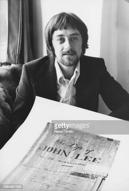 Portrait of musician Dave Swarbrick with a poster of 'The Life of John Lee' and his fiddle January 16th 1975