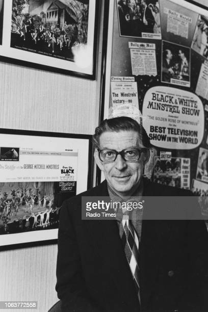 Portrait of musician George Mitchell with posters for his Black and White Minstrel Show May 1974