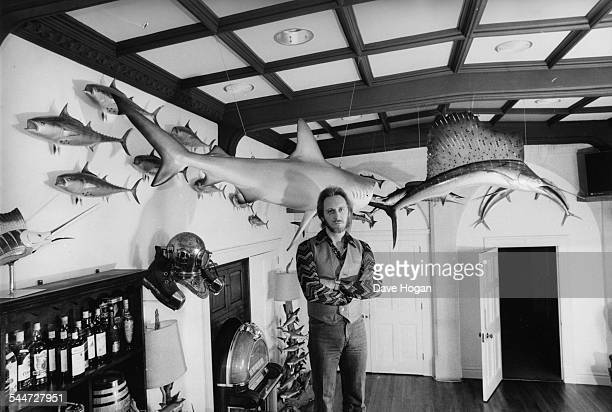 Portrait of musician John Entwistle of the band 'The Who' posing in his home with his huge models of fish circa 1985