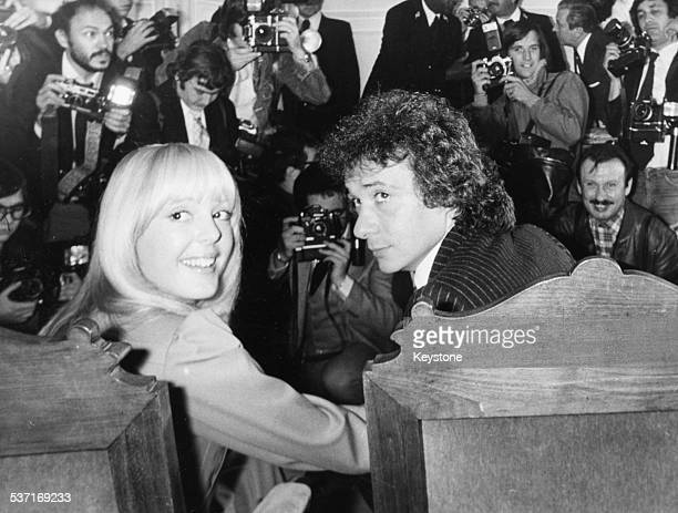 Portrait of musician Michel Sardou and his bride Elisabeth Haas being photographed by the press following their wedding France 1977