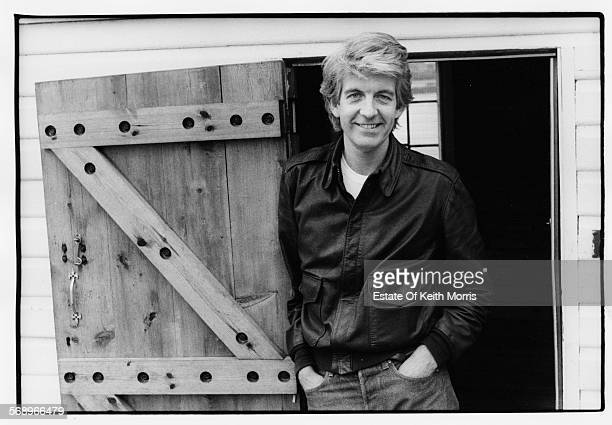 Portrait of musician Nick Lowe wearing jeans and a leather jacket circa 1990