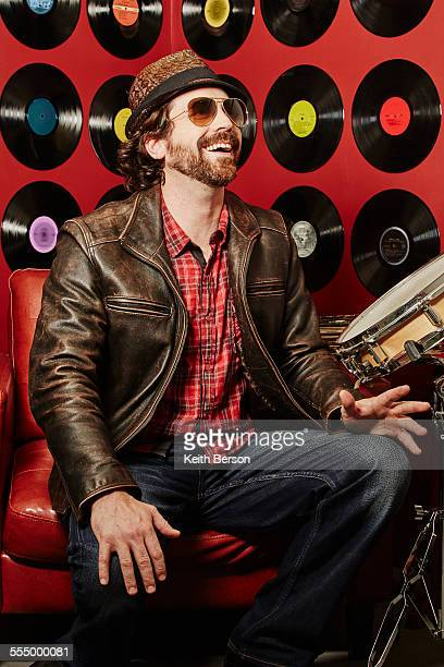 Portrait of musician, vinyl records on background wall