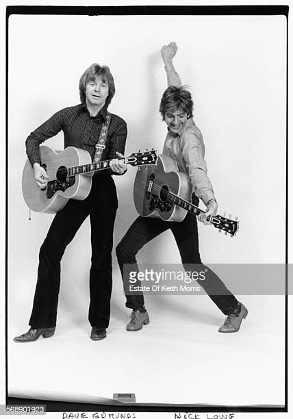 Portrait of musicians Dave Edmunds and Nick Lowe of the pop group 'Rockpile' with their guitars circa 1980