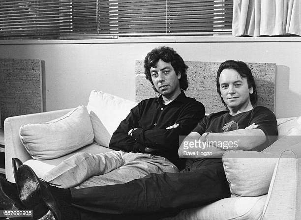 Portrait of musicians Graham Gouldman and Eric Stewart of the band '10 CC' sitting on a couch June 27th 1983
