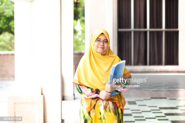 Portrait of Muslim girl in hijab walking in university campus
