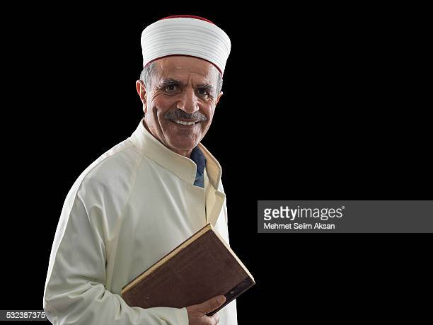 portrait of muslim imam holding koran - imam stock photos and pictures