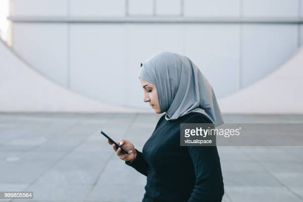 Portrait of muslim woman texting with her smartphone.