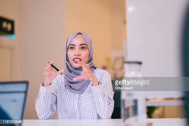 portrait of muslim women having discussion in meeting room - headscarf stock pictures, royalty-free photos & images