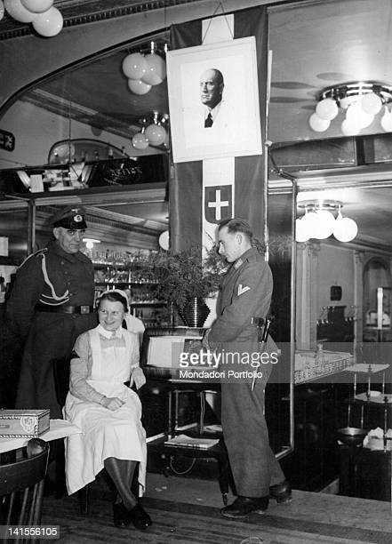 A portrait of Mussolini and the Italian flag hanging in a restaurant for the occupying Axis powers Paris November 1940