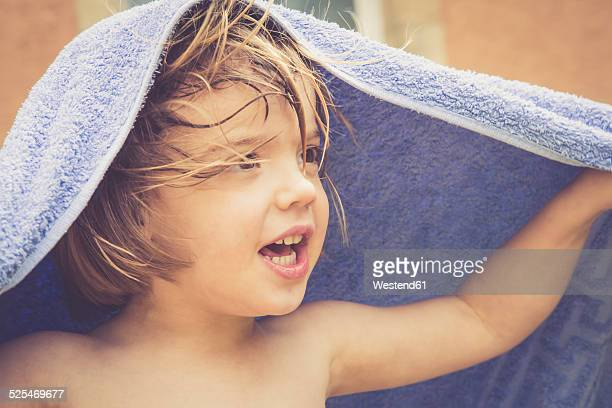 Portrait of naked little girl with a towel on her head