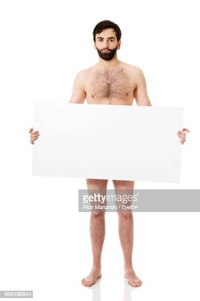 portrait of naked man holding blank placard against white background - hommes nus photos et images de collection