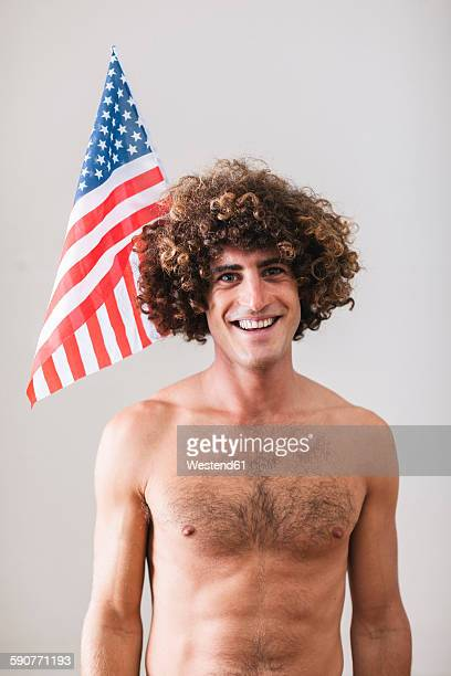 Portrait of naked man with curly hair in front of American Flag