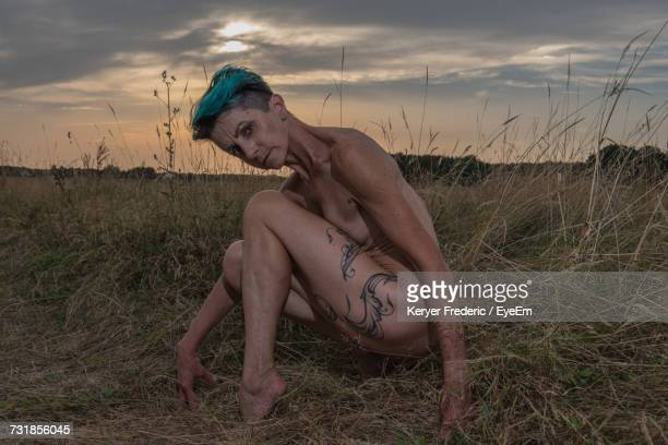 Portrait Of Naked Mature Woman Crouching On Field During Sunset