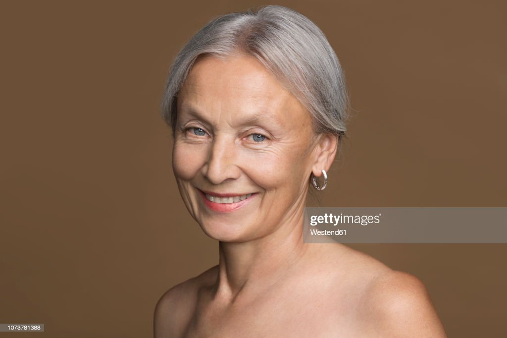 Portrait of naked senior woman with grey hair in front of