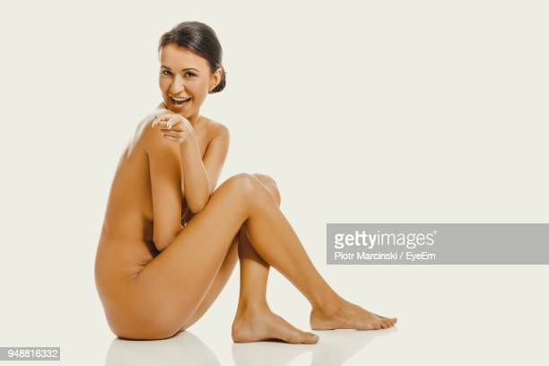 portrait of naked woman laughing while pointing against white background - mulheres jovens mostrando seios imagens e fotografias de stock