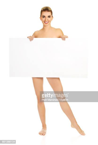 portrait of naked woman with blank placard standing against white background - mujer desnuda cuerpo entero fotografías e imágenes de stock