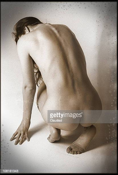portrait of naked woman's backside while she crouches, sepia toned - old nudists stock pictures, royalty-free photos & images