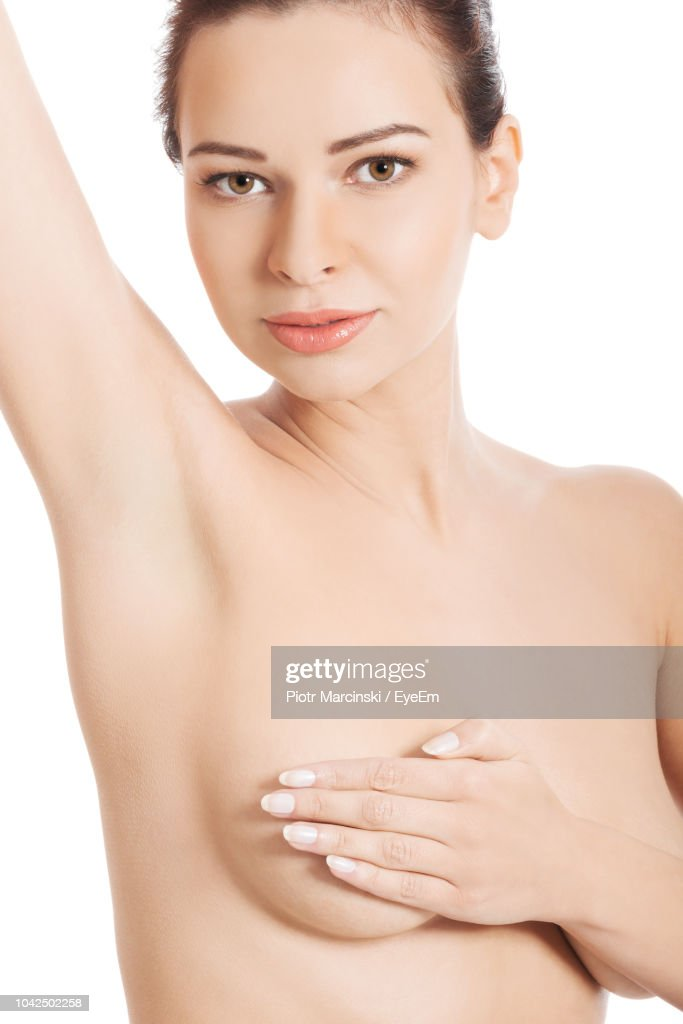 Portrait Of Naked Young Woman Covering Breast While Standing Over White Background : Stock-Foto