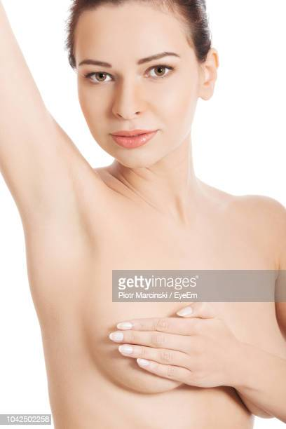 Portrait Of Naked Young Woman Covering Breast While Standing Over White Background