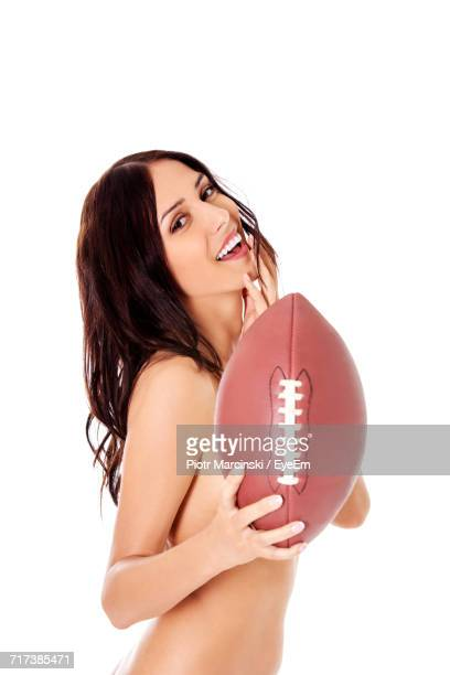Portrait Of Naked Young Woman Holding Rugby Ball Against White Background