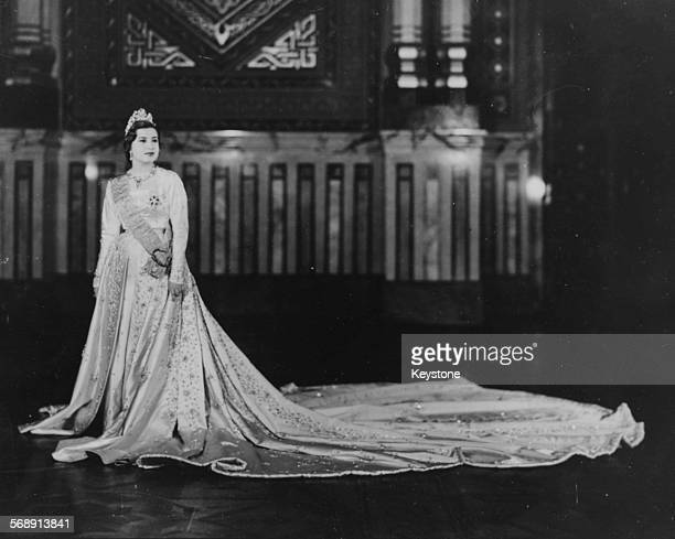 Portrait of Narriman Sadek the bride of King Farouk of Egypt wearing her crown and wedding gown at the Royal Palace Cairo May 19th 1951
