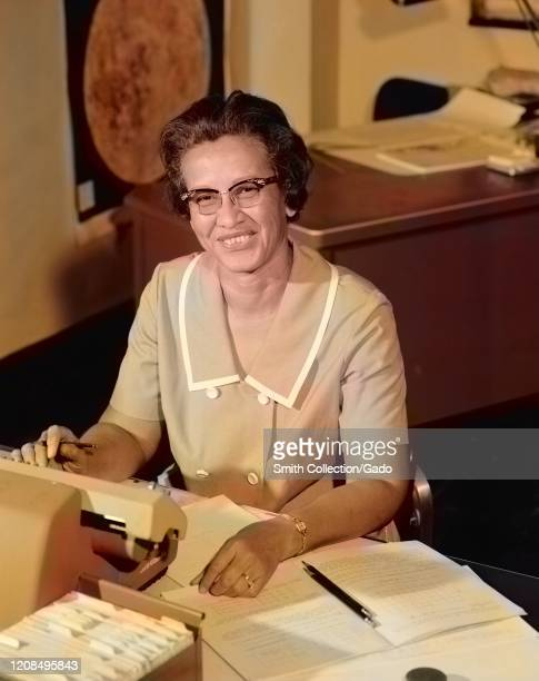 Portrait of NASA human computer and AfricanAmerican mathematical pioneer Katherine Johnson smiling at a desk with notes 1966 Image courtesy NASA Note...
