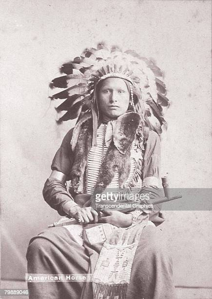 Portrait of Native American man identified as American Horse Deadwood South Dakota early 1900s He wears a feathered headress a breast plate and metal...