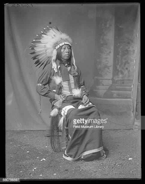 Portrait of Native American Oglala Sioux Edward Bad Hair wearing a feather headdress and holding a feather in his lap at the Louisiana Purchase...