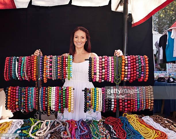 Portrait of necklace shop owner at market