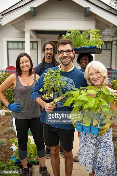 Portrait of neighbors holding plants near house