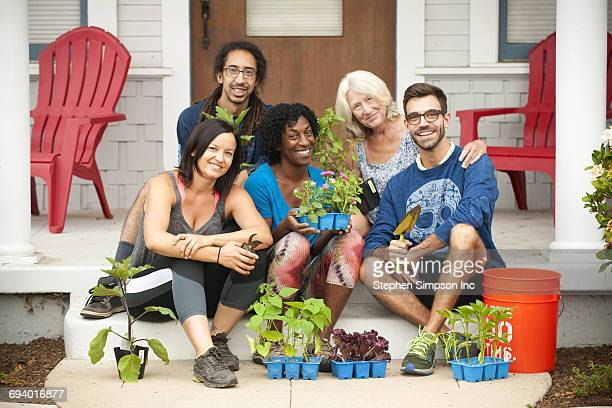 Portrait of neighbors sitting on front stoop holding plants