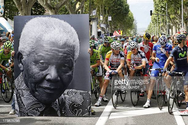 A portrait of Nelson Mandela is displayed in front of cyclists at the kilometer zero to celebrate the birthday of former South African President...