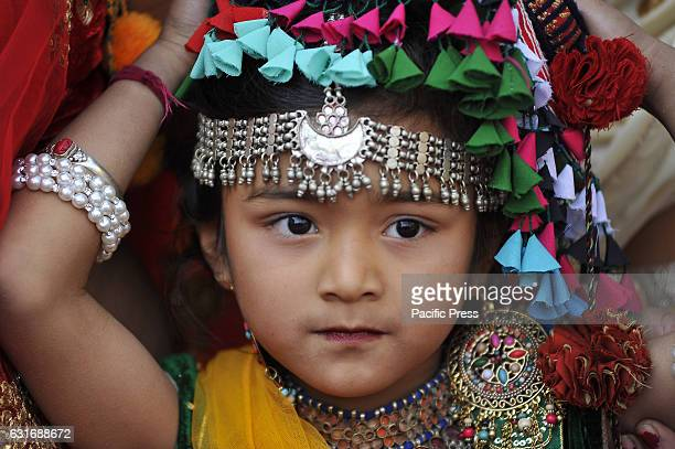 Portrait of Nepalese Tharu community girl in a traditional attire during prade of the Maghi festival celebrations or the New Year of the Tharu...
