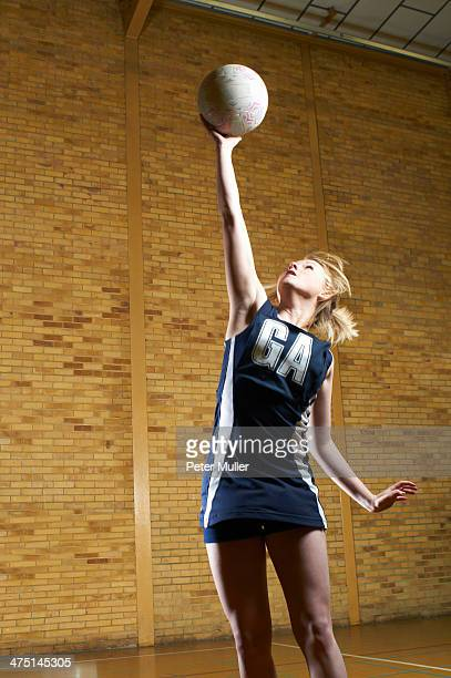 Portrait of netball player reaching for ball