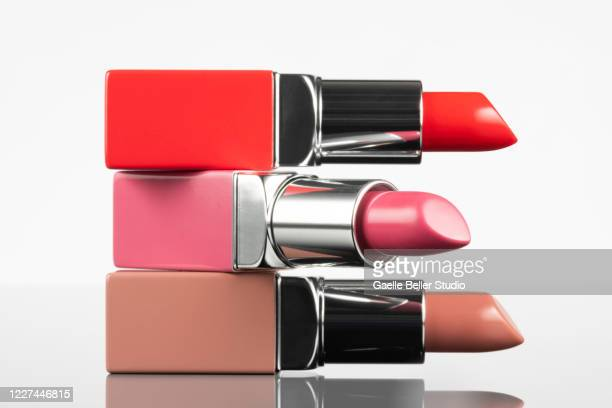 portrait of new lipsticks stacked against white background - pintalabios fotografías e imágenes de stock