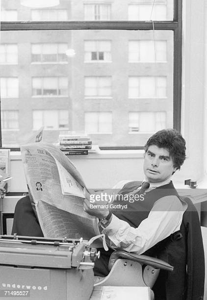 Portrait of New York Magazine editor Jim Brady as he sits at his desk and holds an open copy of the Wall Street Journal New York New York May 1977