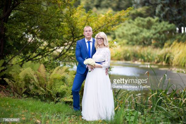 Portrait Of Newlywed Couple Standing By Pond At Park