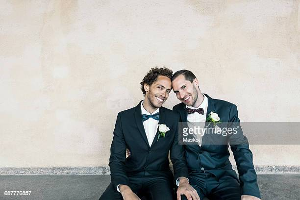 Portrait of newlywed gay couple sitting on bench against wall