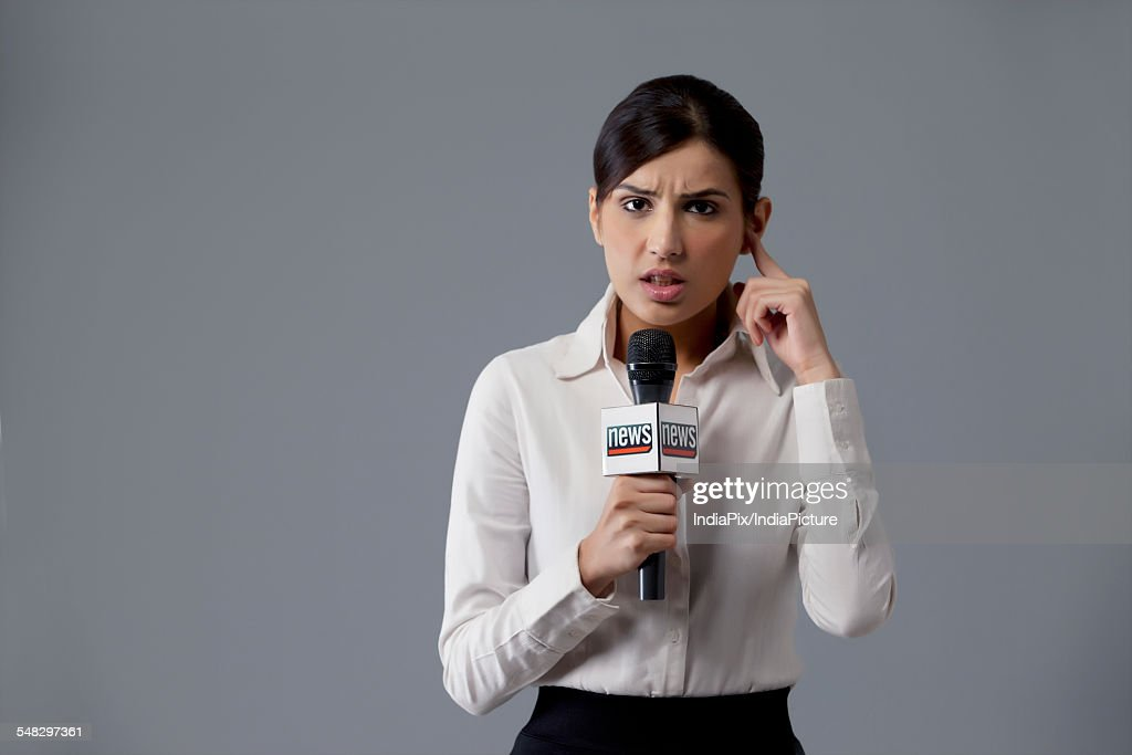 Portrait Of News Reporter Listening Against Colored Background Stock Photo