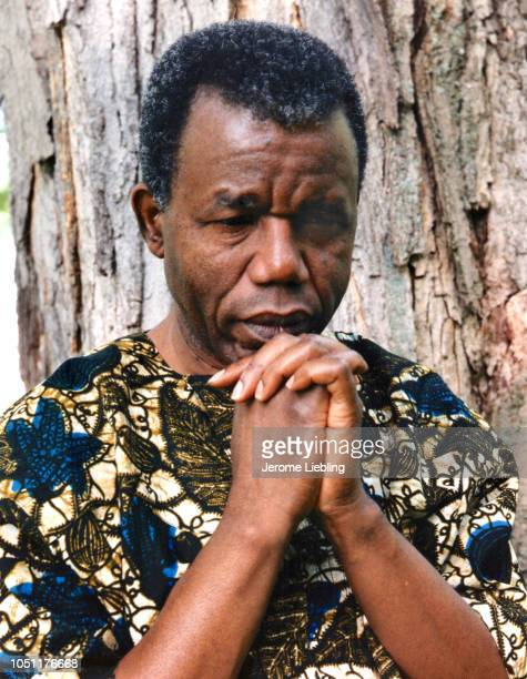 Portrait of Nigerian author professor critic and Igbo chieftain Chinua Achebe dressed in an African dashiki with his chin resting on his hands...