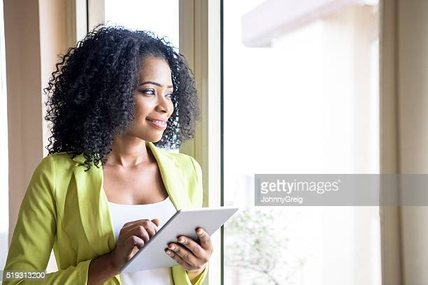 Portrait of Nigerian woman looking through window with tablet